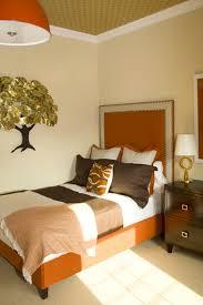 Orange U0026 Brown Bedroom With Glossy Orange Pendant, Orange Headboard, Brown  Shams, Gold Leaf Tree Wall Art, Brown Nightstand And Antique Brass Lamp.