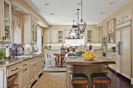 kitchen design cabinets traditional light: richly detailed traditional kitchen design features immense dark wood topped island between large swaths of light