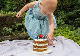 first birthday cake with little girl in blue dress