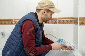 plumber caulking bathtub with silicone glue using caulking