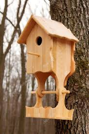 wooden house with a feeding trough for birds stock photo