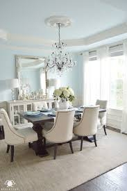 horizontal buffet mirror crystal chandelier in elegant blue dining room with restoration hardware trestle