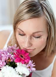 beautiful woman smelling a bunch of