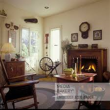 living room country living room wood mantel fireplace wall clock painted red coffee table rocking chair braided rug wood floors child s chair