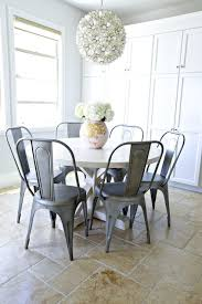 fabulous dining nook features lotus flower chandelier over round cross leg dining table surrounded by tolix chairs