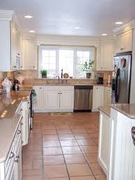 white huntwood cabinets withtyphoon bordeaux granite and saltillo tile for traditional kitchen design