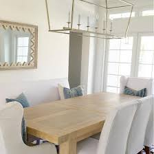 dining room neutral dining room coastal white and blue dining room with darlana linear chandelier white slipcovered chairs and denim pillows by jp cajuste