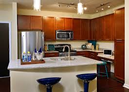 Nice Glass Pendant Lamps Over White Marble Countertops Kitchen Island With  Sink And Blue Stools As Well As Brown Cabinetry Set In Small Space Kitchen  ...