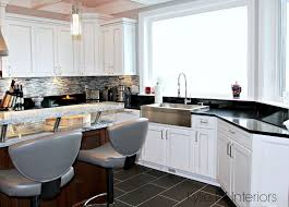 high contrast whtie kitchen with black countertops and farmhouse stainless sink kylie m interiors