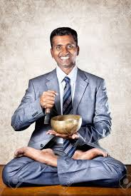 meditation businessman office. indian businessman doing yoga meditation with tibetan singing bowl on the table in office at d