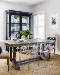 small living room boasts a ghost dining chairs placed on a seagr rug in front of