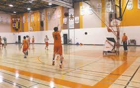 a member of the yorkton regional high raiders senior boys basketball team practices his long range game as coach payne looks on