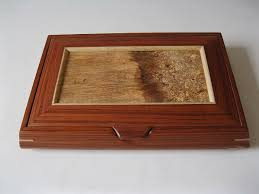 this wooden jewelry box has a lid that lifts to reveal trays with various dividers
