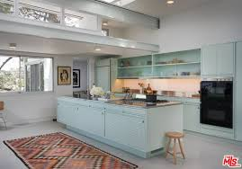 the home features a single wall kitchen with a large center island along with seafoam green cabinets