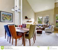 large beige bright living room with dining room table with diffe color chairs