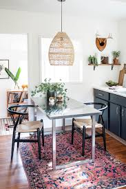 boho rattan pendant lighting over dining room table in kitchen with vintage persian rug wishbone