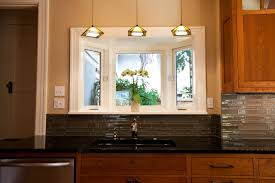 lighting over kitchen sink. three beautiful pendant lamps over the kitchen black sink plus its gold tone faucet a small lighting