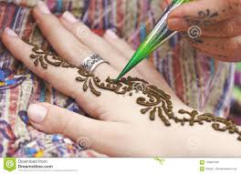 художник крася традиционную индийскую татуировку хны на руке женщины