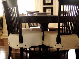 simple dining room with simple white slip cover for chair on dark wooden chairsand solid hardwood