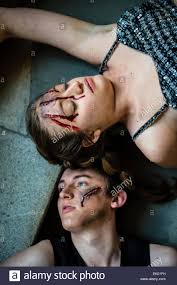 sfx special effects make up a woman and a man actors with deep cuts and gouges on their foreheads created by using se film and television makeup