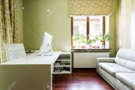 comfortable home office. Cosy, Home Office Interior With The Sofa, Desk, Comfortable Armchair And Window Stock