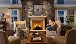 comfortable white armchairs with rustic coffee table and eldorado stone for traditional family room design