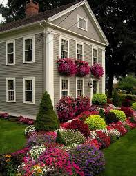 Exterior. assorted color flowers and plants on the green grass in front of  gray house