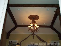 bedroom ceiling with open beam ceiling and ornate chandelier
