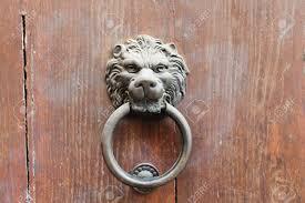 lion head shaped old bronze door handle with ring in urban door stock photo 16862795