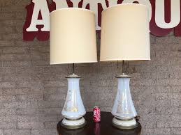 pair of white milk glass lamps with gold bird and plant motif on painted wooden base