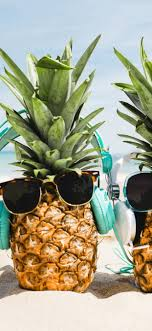 Two pineapples, sunglasses, beach ...