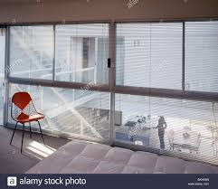 Modern Bedroom Blinds Charles Eames Chair In Front Of Glass Wall With Blinds In Modern