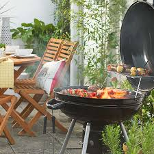 black charcoal bbq with wooden garden table and chairs in background