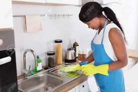 African Young Woman Cleaning Kitchen Sink With Spray Bottle In