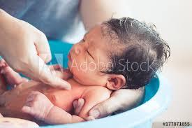 cute asian newborn baby girl take a bath in bathtub mom cleaning her baby