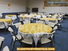 white plastic chairs with round table with white table cloth and yellow overlay diamond