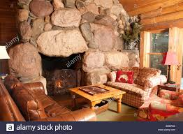 huge stone fireplace with fire burning in elegant country wood home backgammon game on table across from couches and chair huge h71 fireplace
