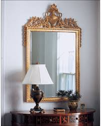 empire style decorative wall mirror framed in gold leafed carved wood frame with urn and swags
