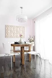 reclaimed wood round dining table lined with white dining chairs west elm scoop back dining chairs alongside a west elm whitewashed wood wall art