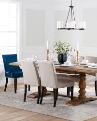 a transitional dining room with a beautiful wooden trestle table upholstered seating blue velvet