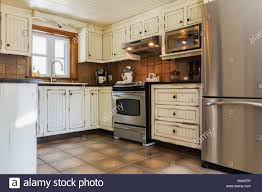 Kitchen With Cream Coloured Antique Finish Wooden Cabinets Ceramic