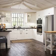 A white open kitchen with vaulted ceiling with white drawers and doors and  black handles and ...