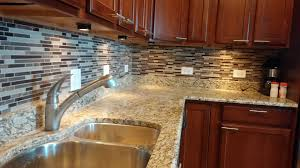 glass mosaic tiles and puck lights were installed to accentuate this kitchen in chicago cabinet lighting puck light