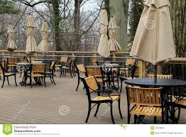 peaceful scene of tables and chairs with tied umbrellas on outdoor restaurant patio stock photo image of outdoor tables 52623894