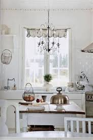 shabby chic white kitchen with chandelier lighting fixtures
