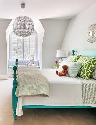 gender neutral kids room with teal 4 poster bed and green nightstand