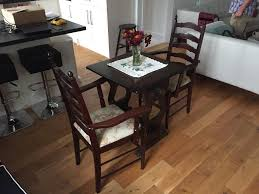 small dark wood dining table with 2 chairs