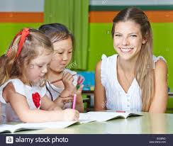 Nursery Teacher Happy Nursery Teacher With Kids Drawing In A Kindergarten Stock