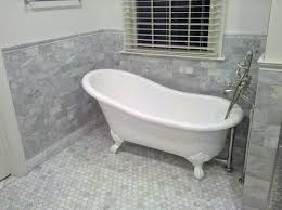 bathroom mosaic floor tile with light grey stone bathroom wall tile and white freestanding bathtub also small window