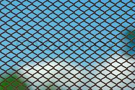 Chain link rusty fence on a blue sky background Stock Photo
